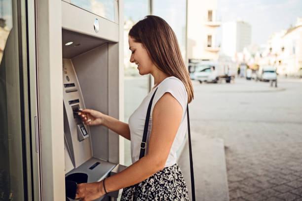 Frau zieht Geld am Outdoor-Geldautomaten ab – Foto