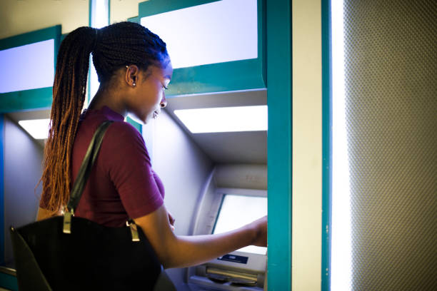 Woman withdrawing money from a cash machine stock photo