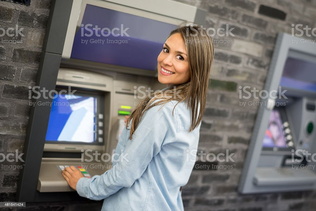 Woman withdrawing money from an ATM stock photo