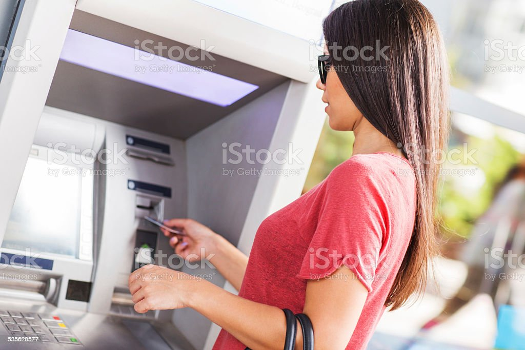 Woman withdrawing money from ATM. stock photo