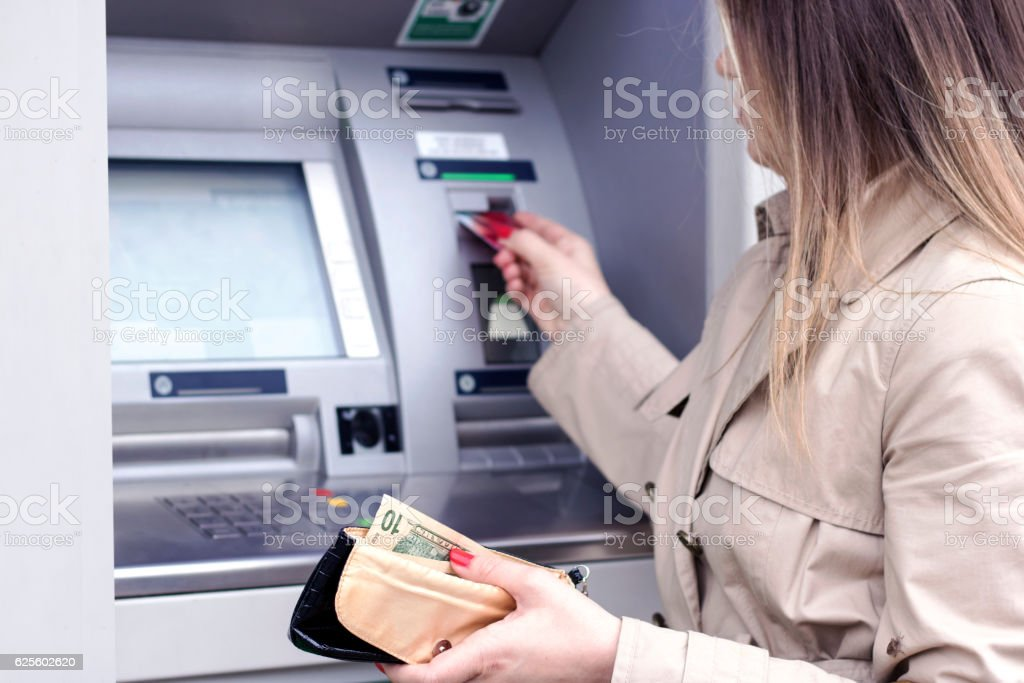 Woman withdrawing money from ATM stock photo