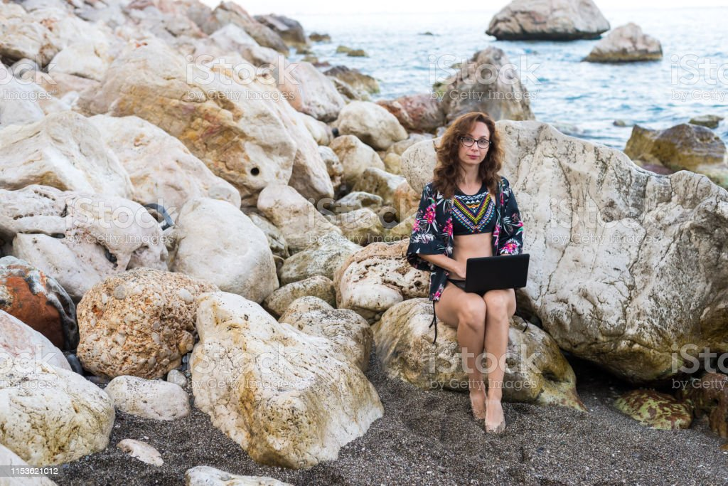 Woman workaholic works on netbook sitting on a stone on the beach....