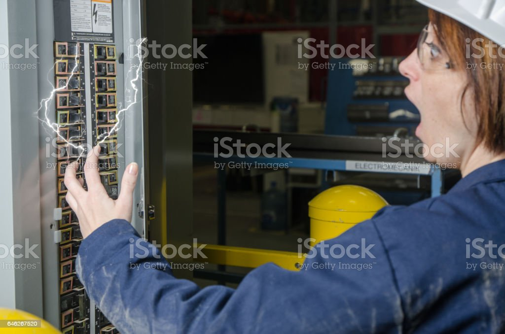 Woman worker being electrocuted at a fuse box stock photo