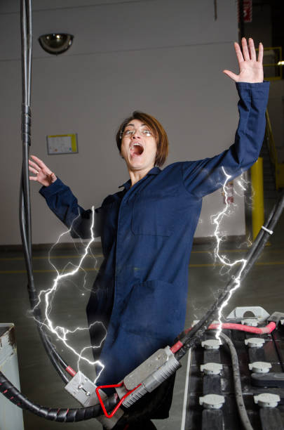 Woman worker being electrocuted by battery electricity sparks stock photo