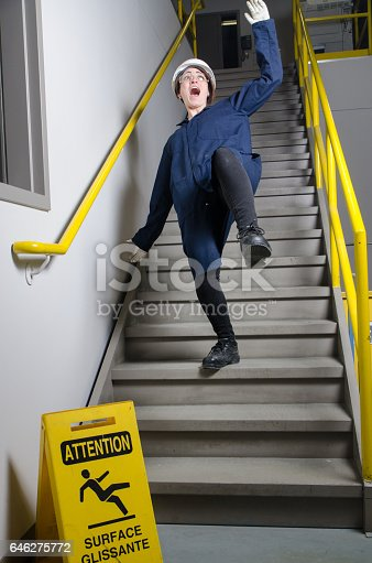Woman worker falling down the stairs in a factory.