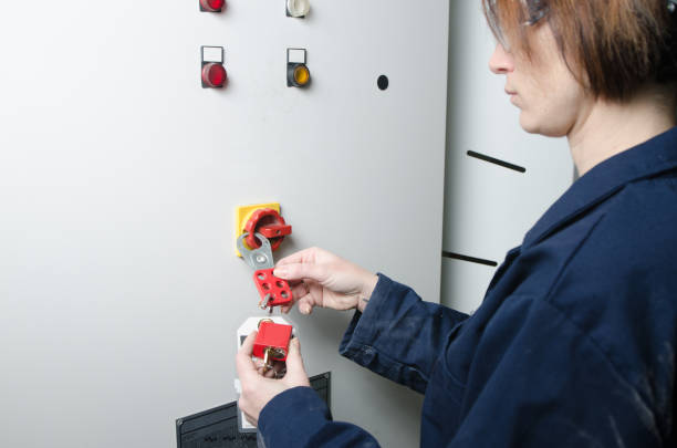 Woman worker locking out electrical box Woman worker locking out electrical box for safety before servicing an equipment lockout stock pictures, royalty-free photos & images