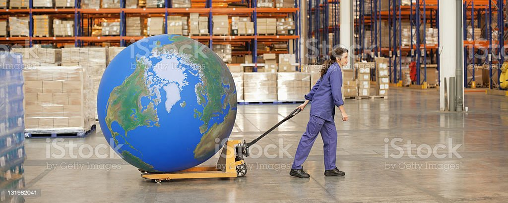 Woman worker pulling large blue ball on hand truck in warehouse stock photo