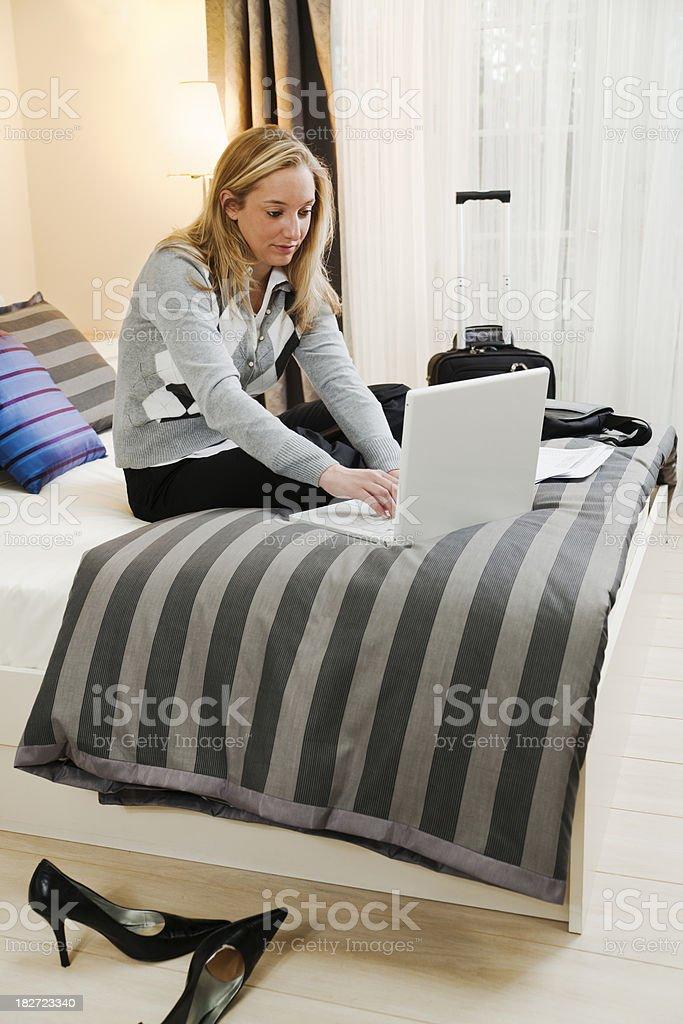 \'Subject: Vertical view of a young blonde woman sitting on the bed in...