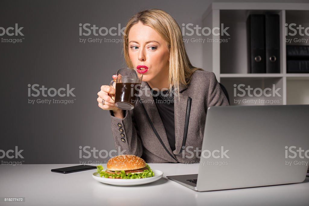 Woman working and having coffee and burger for lunch stock photo