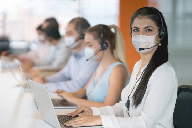 Woman working as a customer service representative at a call center and wearing facemask stock photo