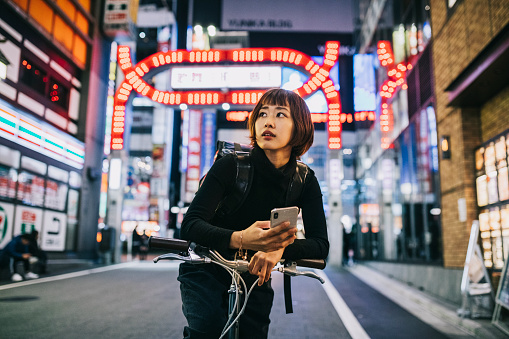 Young Asian Woman working for an food delivery app company. Using Smartphone to navigate in the big city,