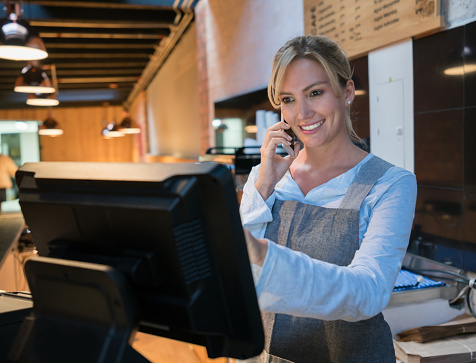 istock Woman working at a bakery talking to a customer on smartphone and registering the takeout on the system 931275644