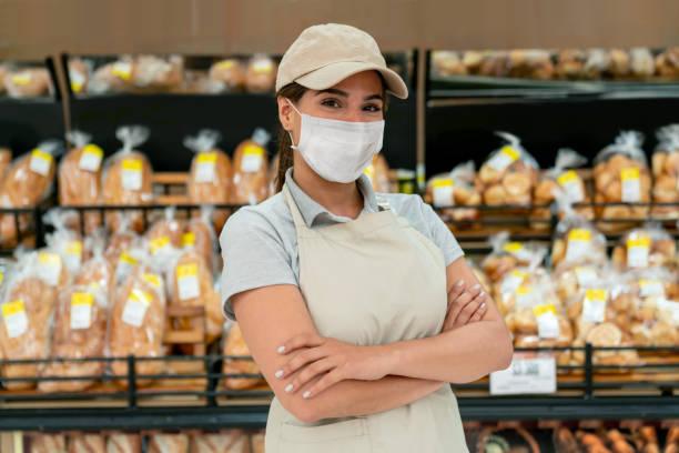 Frau arbeitet in einer Bäckerei mit einer Gesichtsmaske, um das Coronavirus zu vermeiden – Foto