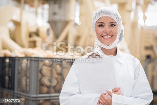Woman working at a bread factory doing quality control and wearing a uniform