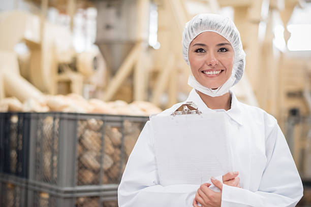 woman  working at a bread factory - stapelvoedsel stockfoto's en -beelden