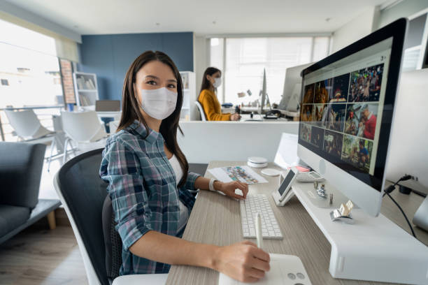 Woman working at a creative office on her computer while wearing a facemask stock photo