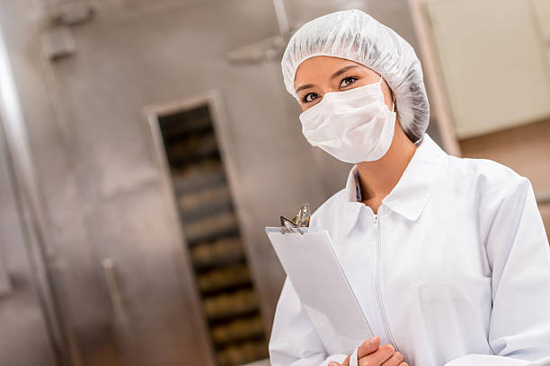 Woman working at a food factory Woman working at a food factory holding a clipboard and wearing a uniform hair net stock pictures, royalty-free photos & images