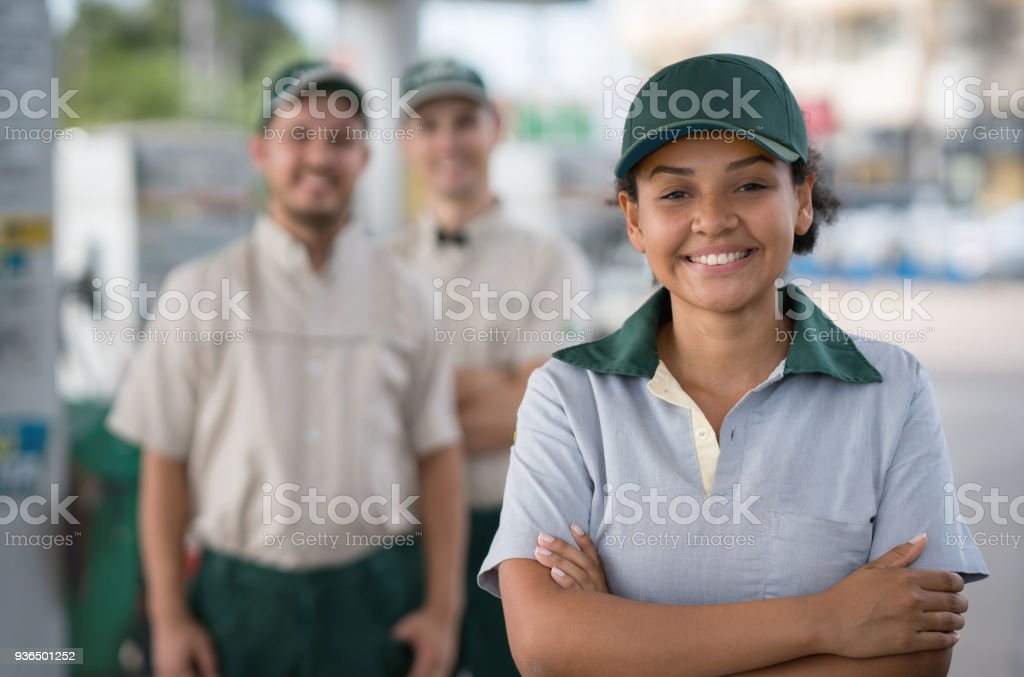 Woman working at a gas station leading a team and looking happy stock photo