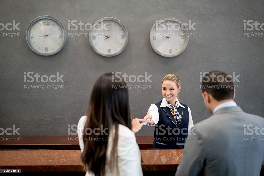 Woman working at a hotel doing the check in stock photo