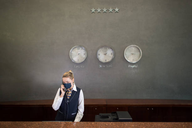 Woman working at a hotel's reception wearing a facemask stock photo