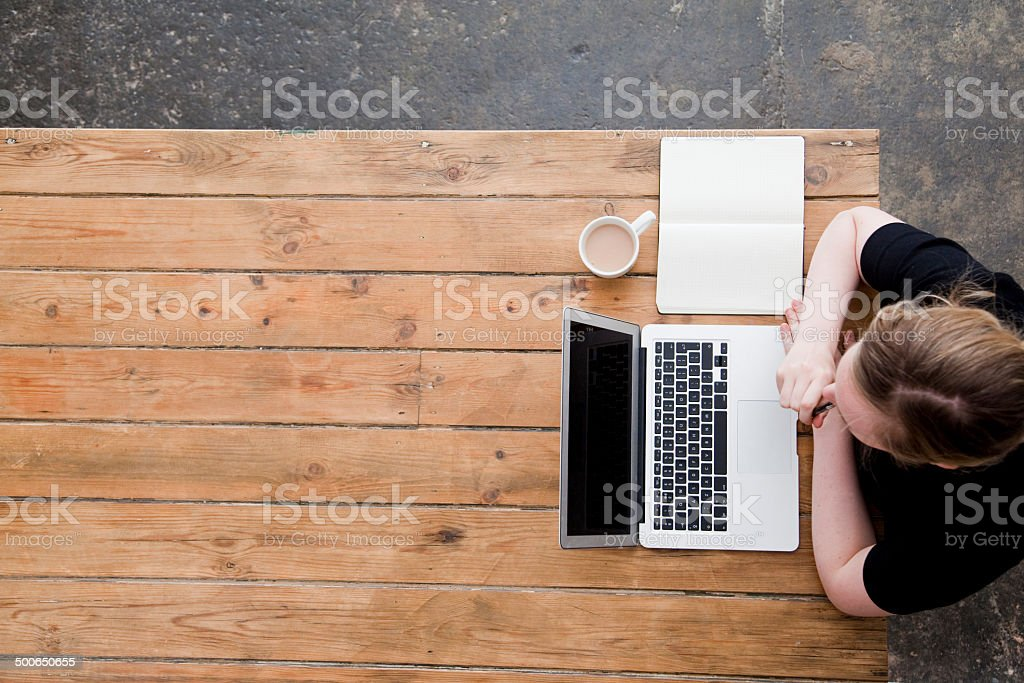 Woman working at a laptop photographed from directly above royalty-free stock photo