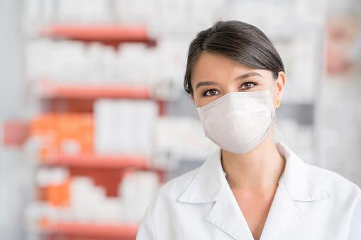 Frau Die Während Der Covid19pandemie In Einer Apotheke Arbeitet Und Eine Gesichtsmaske Trägt Stockfoto und mehr Bilder von Ansteckende Krankheit