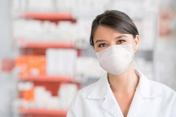 Woman working at a pharmacy and wearing a facemask during the COVID-19 pandemic stock photo