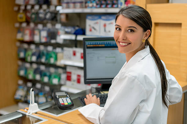 Woman working at a pharmacy Happy woman working at a pharmacy on the till behind the counter sales clerk stock pictures, royalty-free photos & images
