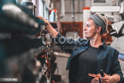 An independent female mechanic working at an auto repair shop. She is looking for the right tools to use in her workshop.