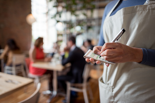 Close-up on a woman working at a restaurant as a waitress and holding a notepad