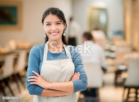 Portrait of a happy Latin American woman working at a restaurant and looking at the camera smiling