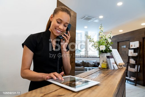 Woman working at a spa talking on the phone and making a booking - small business concepts. ****DESIGN ON SCREEN IS OURS**