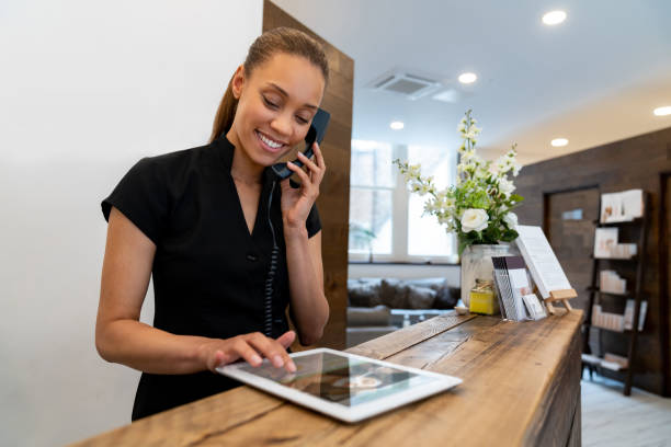 woman working at a spa talking on the phone - receptionist stock photos and pictures