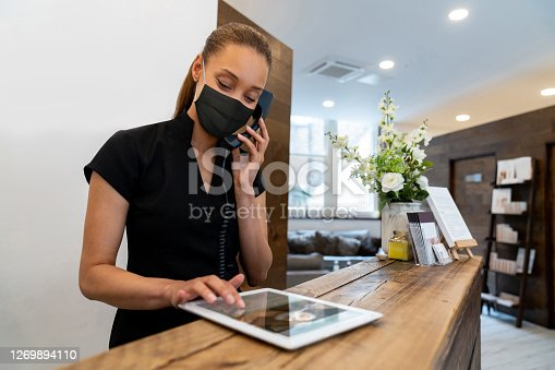 Woman working at a spa wearing a facemask while talking on the phone during the COVID-19 pandemic - lifestyle concepts