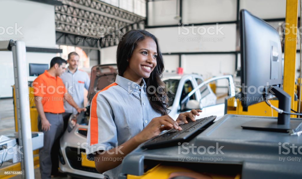 Woman working at an auto repair shop stock photo