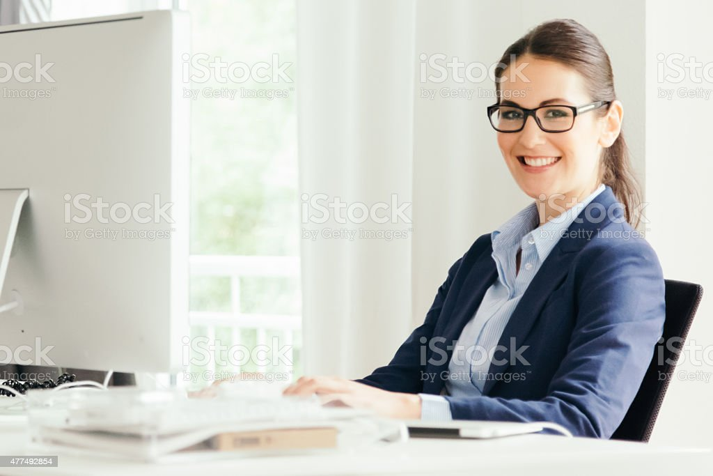 Woman working at computer in modern office stock photo