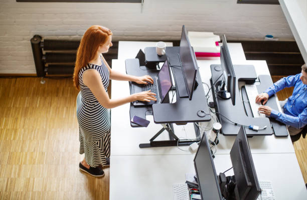 Woman working at ergonomic standing desk stock photo