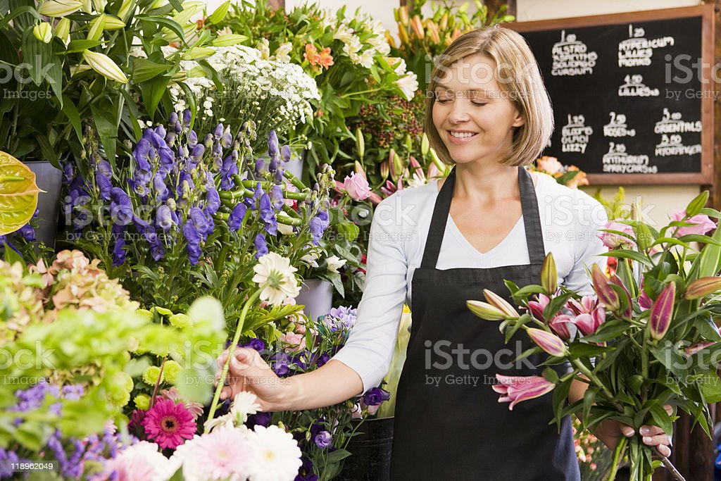 Woman working at flower shop smiling stock photo