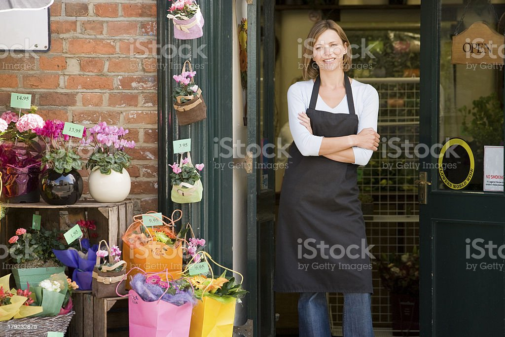Woman working at flower shop smiling royalty-free stock photo