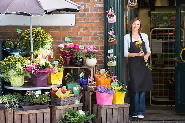 femme travaillant au fleuriste souriant - fleuriste photos et images de collection