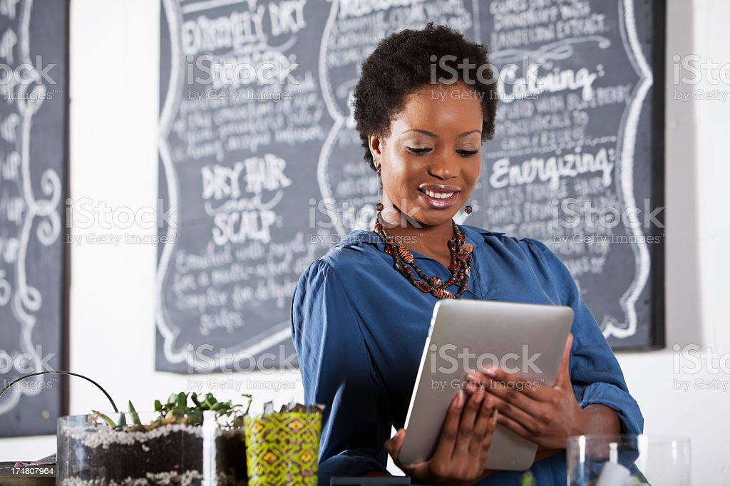 Woman working at hair salon, using digital tablet stock photo