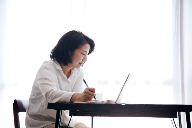 Woman working at home Japanese woman in casual clothes checking and writing the schedule on diary on the desk. only japanese stock pictures, royalty-free photos & images