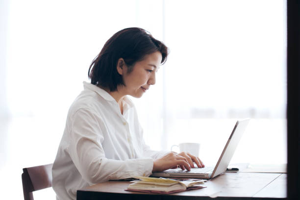 Woman working at home Japanese woman in casual clothes using a laptop and working on the desk. only japanese stock pictures, royalty-free photos & images