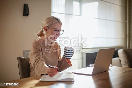 Woman working in her kitchen while having breakfast