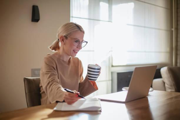 mulher que trabalha em casa ao tomar o pequeno almoço - working in café - fotografias e filmes do acervo