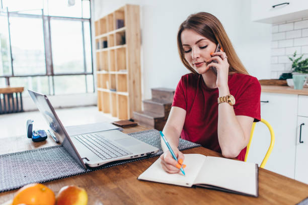 Woman working at home write notes while talking on phone stock photo