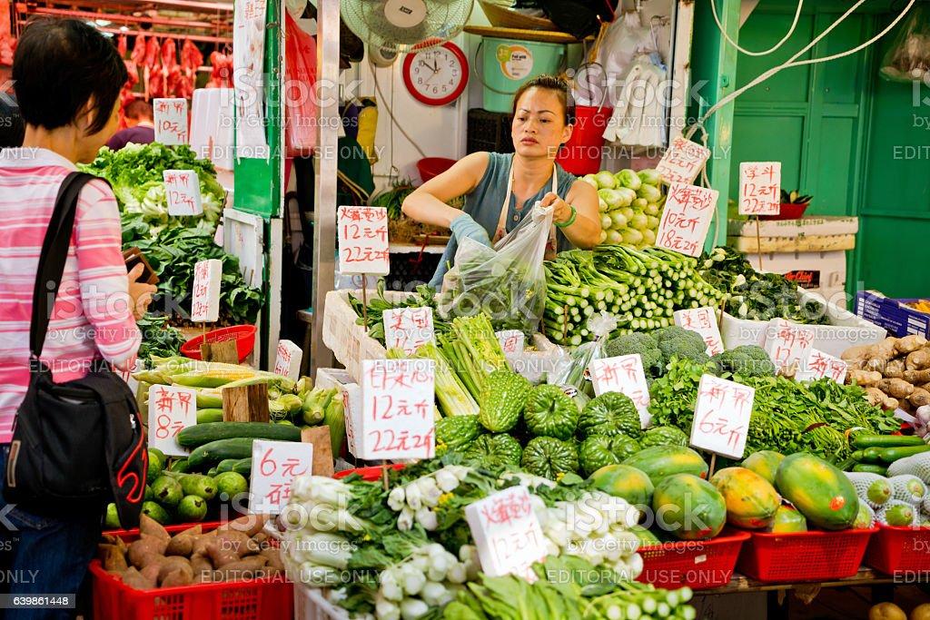 Woman working at market stall, Hong Kong stock photo