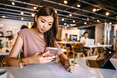 Woman using mobile phone while writing notes at modern office