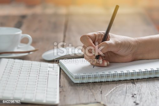 istock Woman working at old wooden table. 640298762