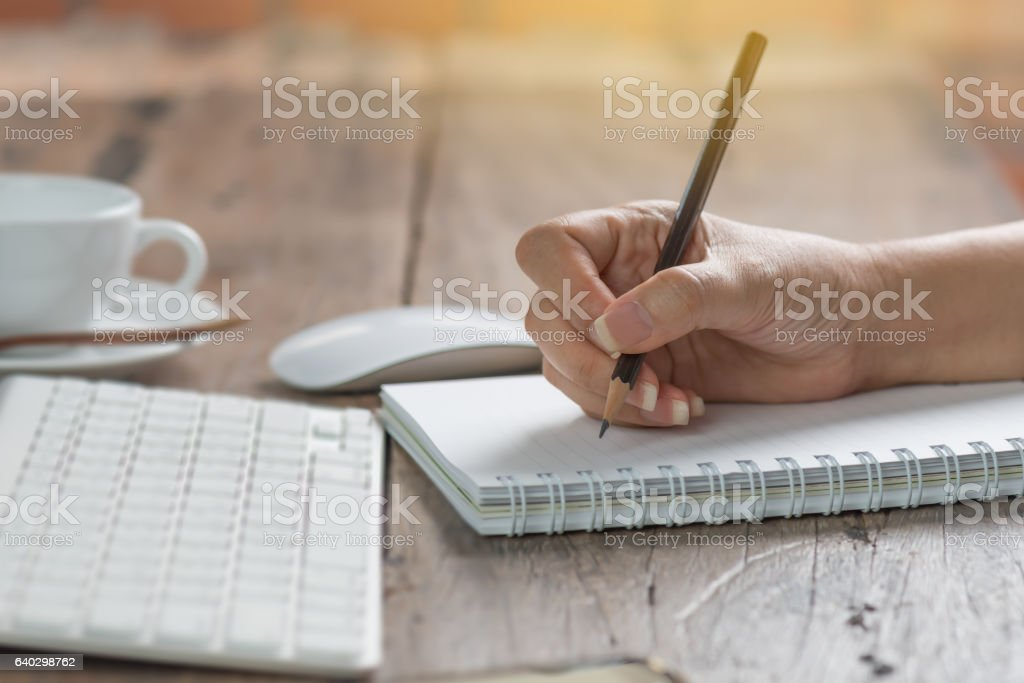 Woman working at old wooden table. stock photo